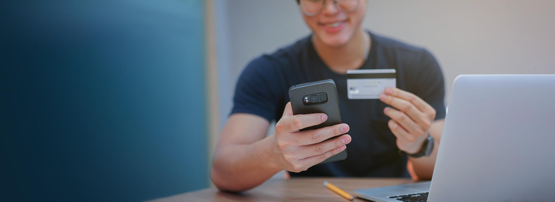man holding credit card on pay day looking at phone