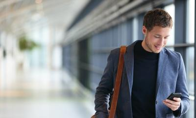 Smartly dressed smiling employee in hallway on mobile phone