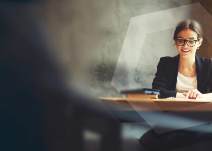 woman with glasses at desk with blurred background